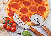 Fresh round baked Pepperoni italian pizza with wheel cutter and knife with tomatoes and basil on light background with linen towel. Macro