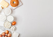 Fresh dairy products on white table background. Glass of milk, bowl of sour cream and cottage cheese and eggs. Fresh baked bagel. Steel whisk. Top view.Space for text