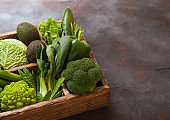 Assorted green toned raw organic vegetables in wooden box on dark background. Avocado, cabbage, cauliflower and cucumber with trimmed and mung beans and pepper and broccoli with sparagus tips.