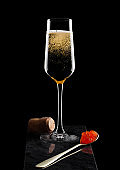 Elegant glass of yellow champagne with red caviar on golden spoon and cork on marble board on black background.