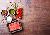 Tray with raw minced homemade beef meat with spices and herbs. Top view and space for text. On top of wooden kitchen table background. With pepper salt and tomatoes.