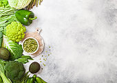 Assorted green toned raw organic vegetables on white stone background. Avocado, cabbage, broccoli, cauliflower and cucumber with trimmed beans and split peas in white bowl. Space for text