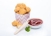 Crunchy chicken popcorn bites in kids paper cup for fast food meals on white background with wooden fork and ketchup.