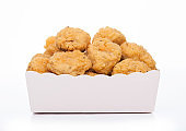 Crunchy chicken popcorn bites in kids paper square cup for fast food meals on white background.