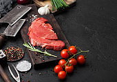 Fresh raw organic slice of braising steak fillet on chopping board with fork and knife on black stone background. Red onion, tomatoes with salt and pepper. Space for text