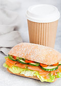 Fresh healthy salmon sandwich with lettuce and cucumber with paper cup of coffee on white stone background. Breakfast snack. Diet food