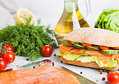 Fresh healthy salmon sandwich with lettuce and cucumber on the plate on white stone background. Breakfast snack. Fresh tomatoes, dill and lemon. Tray of salmon
