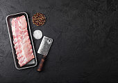 Plastic tray with raw pork ribs and vintage hatchet on black stone background. Pepper with salt. Space for text
