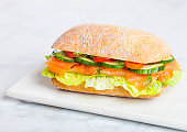 Fresh healthy salmon sandwich with lettuce and cucumber on marble board on white stone background. Breakfast snack. Diet food