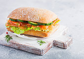 Fresh healthy salmon sandwich with lettuce and cucumber on vintage chopping board on white stone background. Breakfast snack. Diet food