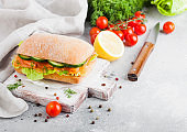 Fresh healthy salmon sandwich with lettuce and cucumber on vintage chopping board on white stone background. Breakfast snack. Fresh tomatoes, dill and lemon. Chopping board and knife