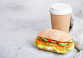 Fresh healthy salmon sandwich with lettuce and cucumber with paper cup of coffee on white stone background. Breakfast snack. Space for text