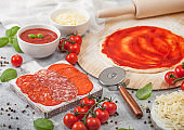 Preparation for baking of pepperoni pizza with raw dough, salami spicy chorizo with wheel cutter and fresh tomatoes and basil on light background with bowl plates with cheese and tomato paste.