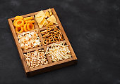 Various snacks in vintage wooden box on black background. Onion rings,nachos, salty peanuts with potato sticks and pretzels. Suitable for beer and fizzy drinks. Top view
