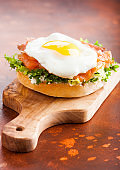 Fresh healthy bagel sandwich with salmon, ricotta and soft egg on vintage chopping board on rustic kitchen table background. Healthy diet food.