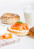 Fresh healthy bagel sandwich with salmon, ricotta and glass of milk on light kitchen table background. Healthy diet food.