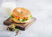 Fresh healthy bagel sandwich with salmon, ricotta and lettuce on vintage chopping board on stone kitchen table background. Healthy diet food. Glass of milk
