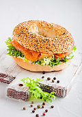 Fresh healthy bagel sandwich with salmon, ricotta and lettuce on vintage chopping board on white kitchen table background. Healthy diet food.