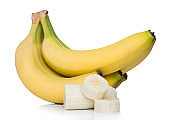 Fresh ripe organic bananas cluster with sliced pieces on white background.