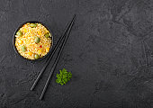 Black bowl with boiled organic basmati vegetable rice with black chopsticks on black stone background. Yellow corn and green peas with paprika slices. Space for text