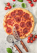 Fresh round baked Pepperoni italian pizza with wheel cutter and knife with tomatoes and basil on light background with linen towel. Top view