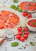 Preparation for baking of pepperoni pizza with salami spicy chorizo with wheel cutter knife and fresh tomatoes and basil on light background with bowl plates with cheese and tomato paste.
