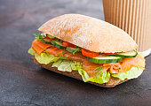 Fresh healthy salmon sandwich with lettuce and cucumber with paper cup of coffee on black stone background. Breakfast snack.