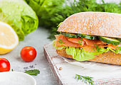 Fresh healthy salmon sandwich with lettuce and cucumber on vintage chopping board on white stone background. Breakfast snack. Fresh tomatoes, dill and lemon.
