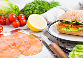 Fresh healthy salmon sandwich with lettuce and cucumber on the plate on white stone background. Breakfast snack. Fresh tomatoes, dill and lemon. Knife and tray with salmon