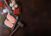 Raw pork loin chops in plastic tray with salt and pepper and vintage meat hatchets and hammer on rusty background.Red pepper, tomatoes and garlic. Space for text