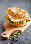 Fresh healthy bagel sandwich with salmon, ricotta and soft egg on vintage chopping board on stone kitchen table background. Healthy diet food.