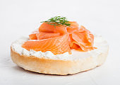 Fresh healthy bagel sandwich with salmon, ricotta and dill on light kitchen table background. Healthy diet food.