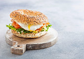 Fresh healthy bagel sandwich with salmon, ricotta and soft egg on vintage chopping board on white kitchen table background. Healthy diet food.