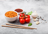 White plate bowl of rice with tomato and basil and garlic and chopsticks on light stone background. Top view.