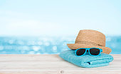 Beach towel, sunglasses and hat on wood over blurred seascape