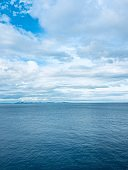 Cloudy sky and sea.  Blue sea with white clouds.
