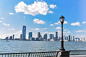 New Jersey skyline from Battery Park in a sunny day. Cityscape view through trees and streetlamp. City and travel concept. Manhattan, New York City, USA