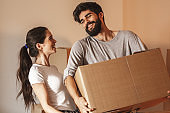 Young couple carrying big cardboard full of home essentials into a new home.