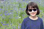 beautiful portrait of smiling child with sunglasses and floral background