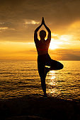 Young Woman in Yoga Tree Pose With Arms Raised Against Beautiful Sunset
