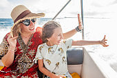Cheerful Single Mother and Daughter Waving From a Boat