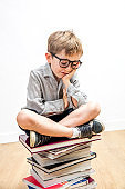 smiling child with bookworm eyeglasses seated on pile of books