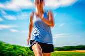 sports woman running at trail - blurred motion