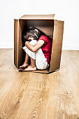 lonely sleeping little tired child hunched in a cardboard box