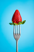 Ripe Strawberry on silver fork against blue background