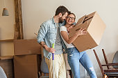 Young couple carrying big cardboard box into new home.Moving house.
