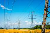 Electricity Pylon in a wheat field with hay bales