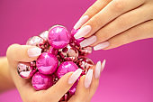 Festive Christmas hands on pink Background with Baby Boomer nails