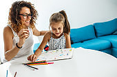 Mother teach her daughter to draw.