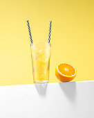 Orange Juice with Ice Cubes and Reusable Drinking Straws